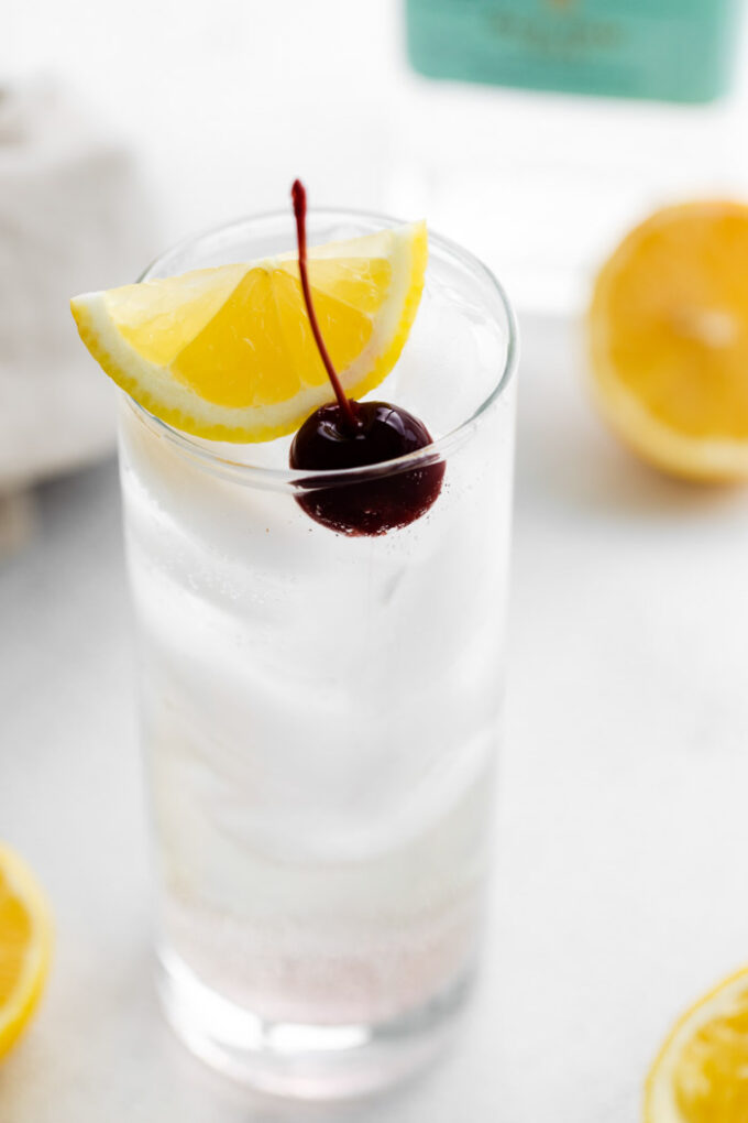 side shot of a tom collins (clear liquid) in a tall glass filled with ice and garnished with lemon wedge and dark cherry