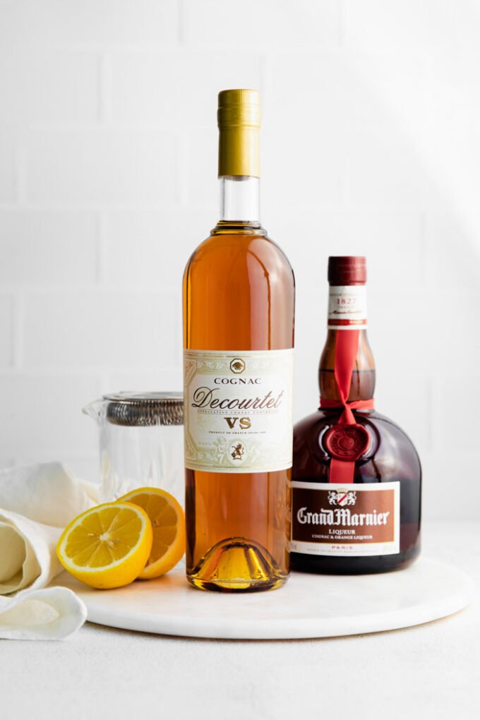 ingredients laid to out make a sidecar drink including lemon juice, cognac, and orange liqueuer