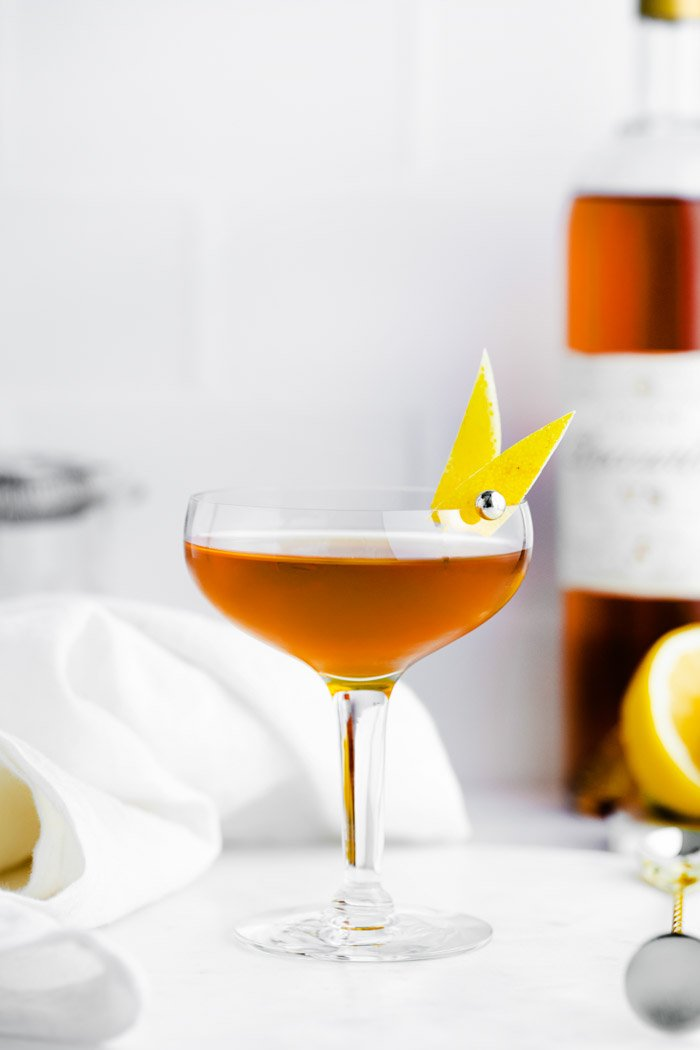 sidecar cocktail in a coupe glass with lemon peel on the side and alcohol bottle on the background