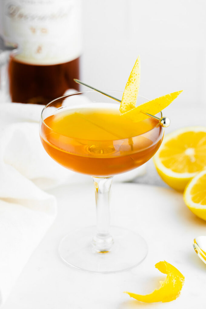 sidecar cocktail in a coupe glass with lemon peel on the side and alcohol bottle on the background as well as oranges