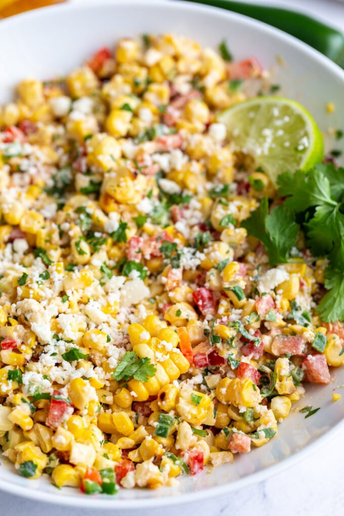 large white bowl of mexican street corn salad topped with cotija cheese and a lime with cilantro in the scene
