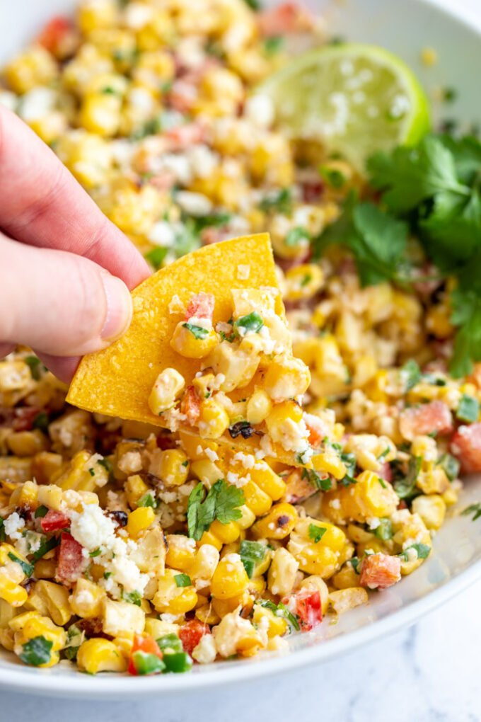 mexican street corn salad in a large bowl with a hand holding a chip scooping up some of the corn salad