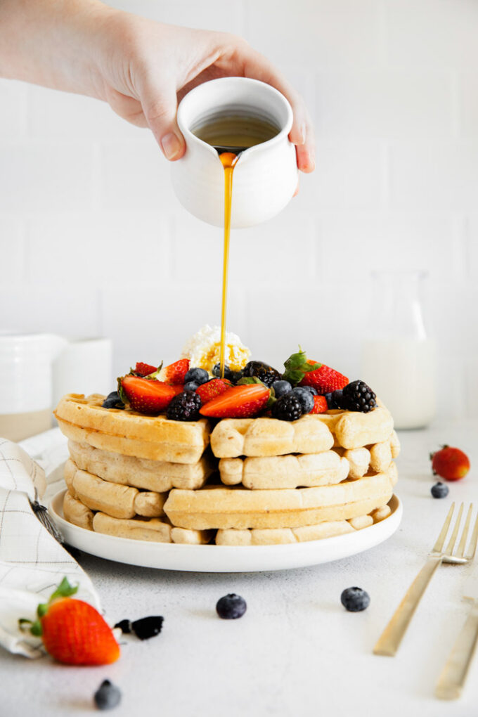 pouring maple syrup over a stack of fluffy vegan waffles