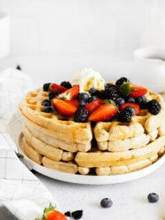 stack of vegan waffles topped with fresh berries and whipped cream