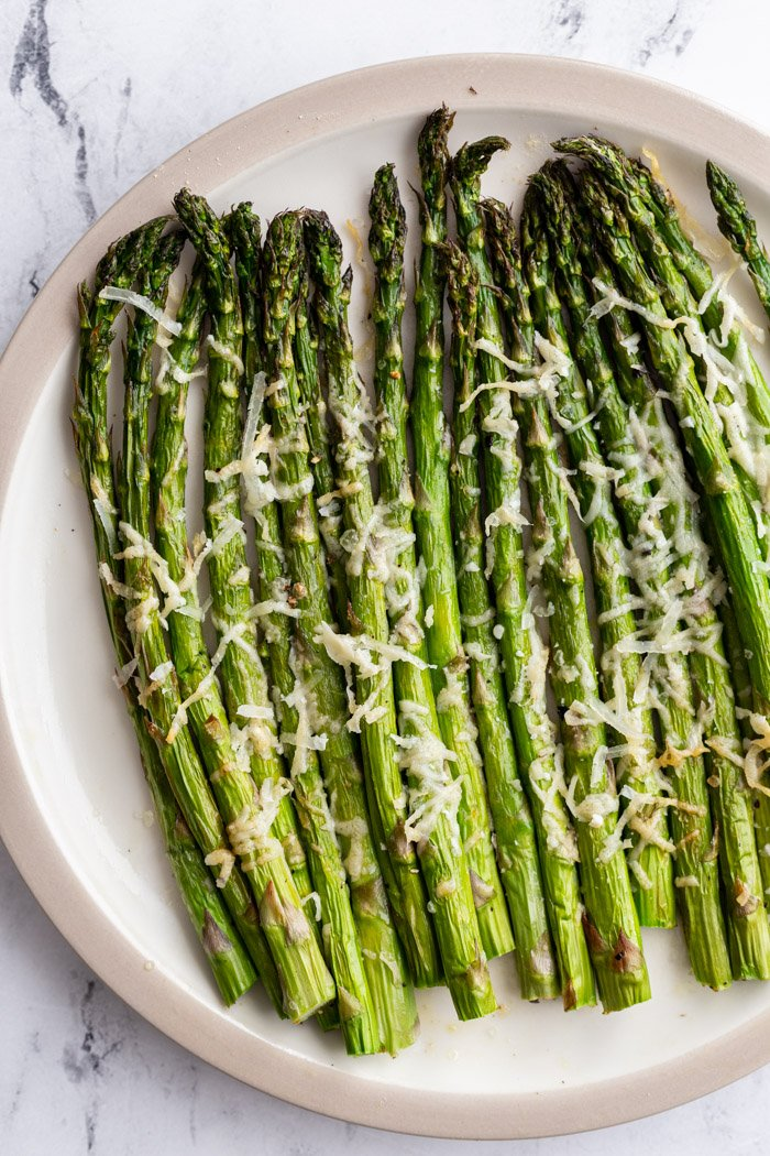 air fryer asparagus topped with parmesan cheese on a serving plate