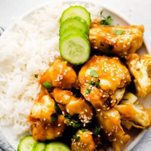 plate filled with white rice, cucumber, and sticky sesame cauliflower