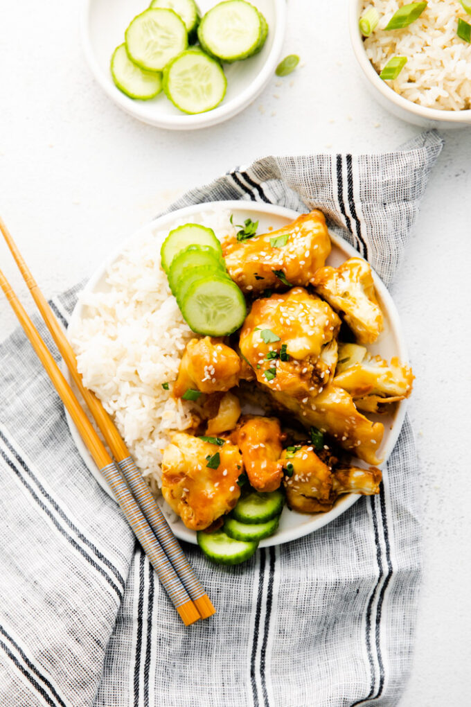 plate filled with white rice, cucumber, and sticky sesame cauliflower. plate on top of a towel with chopsticks on the side