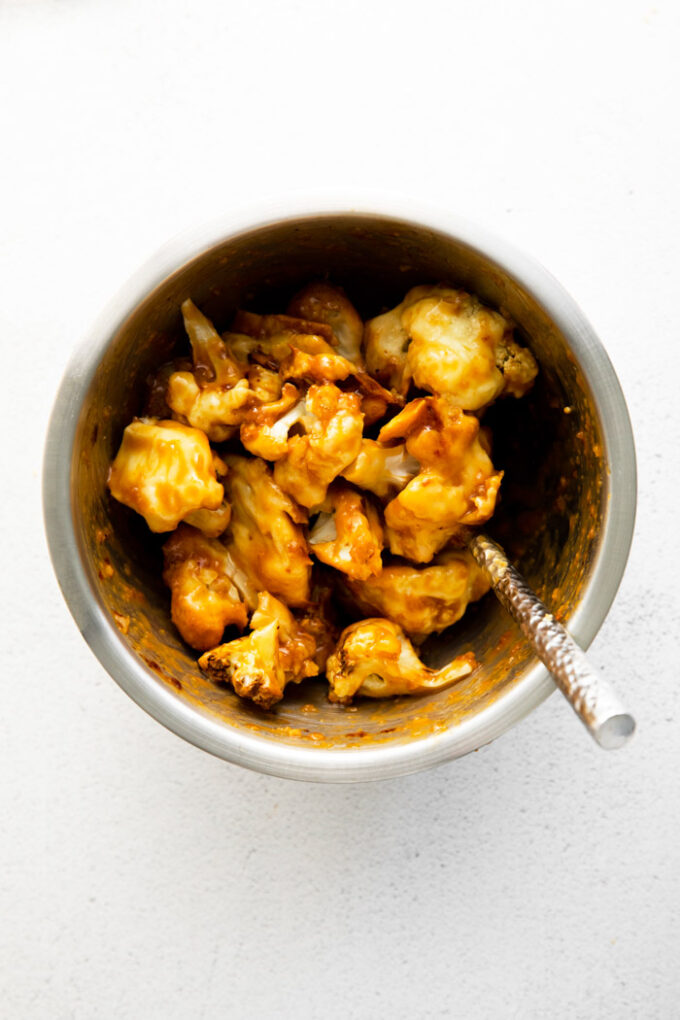 cauliflower florets tossed in an orange sauce inside of a silver mixing bowl