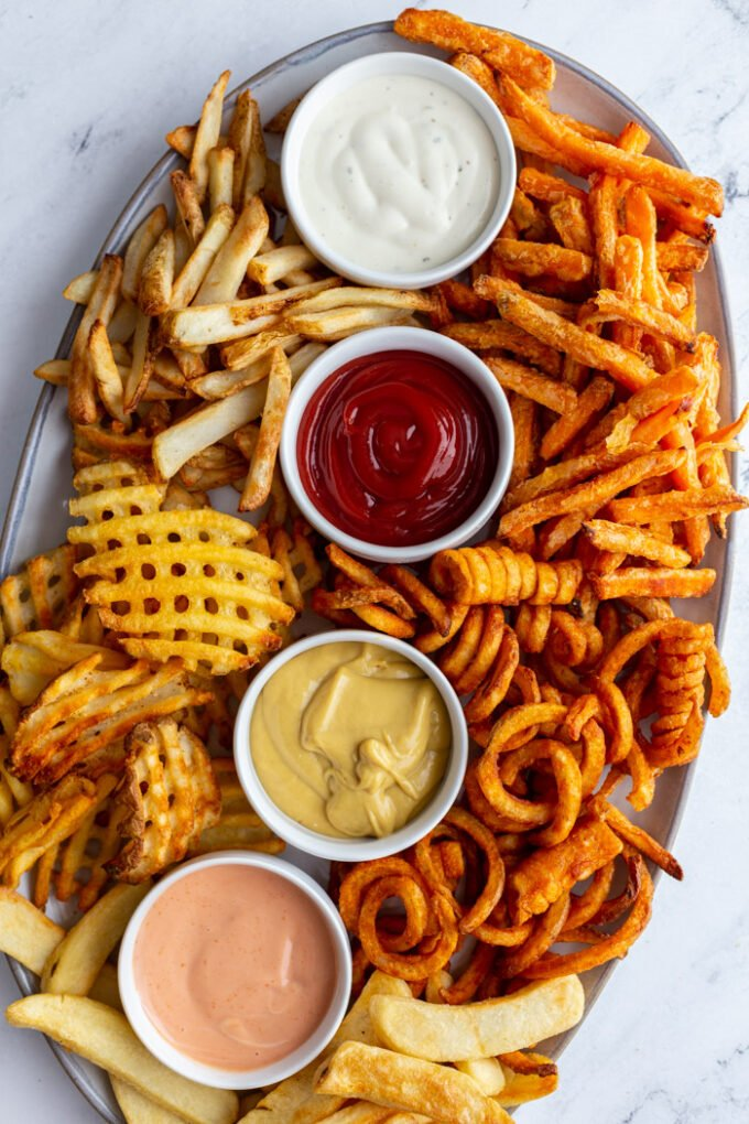 large tray of various kinds of french fries with 4 different flavors and colors of dips in small ramekins