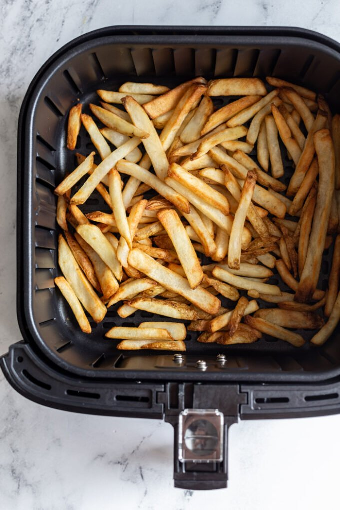black basket of an air fryer with cooked frozen french fries in it