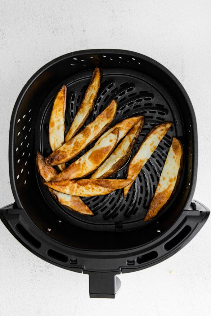 crispy potato wedges in an air fryer basket