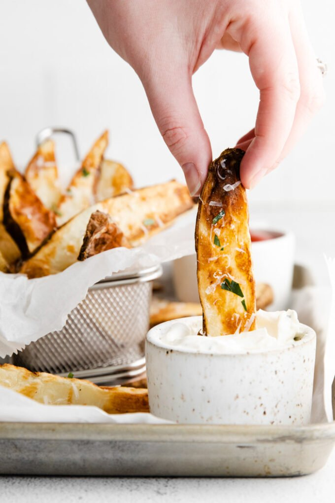 hand dipping a potato wedge in a small bowl of ranch