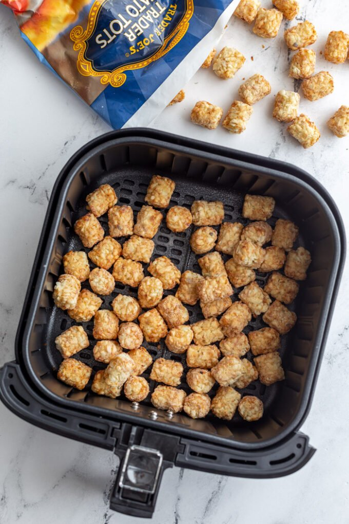 frozen tater tots in air fryer with the bag of tots in the top of the frame