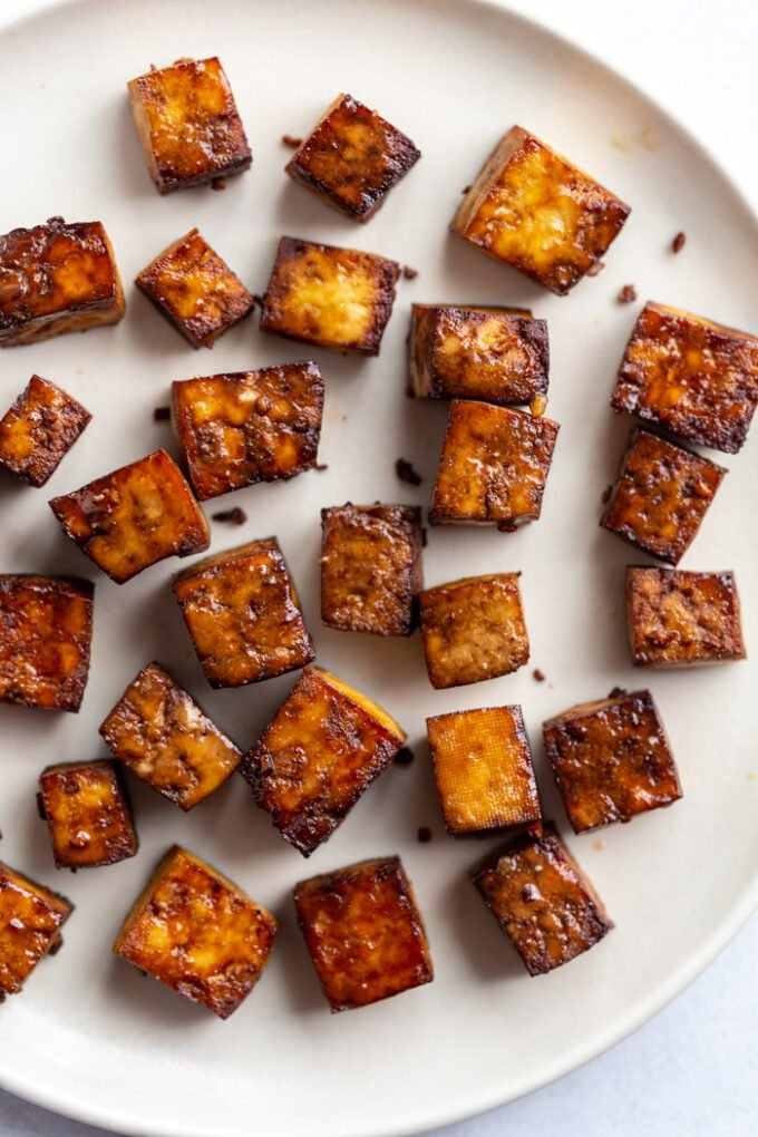 crispy brown tofu cubes on a white plate