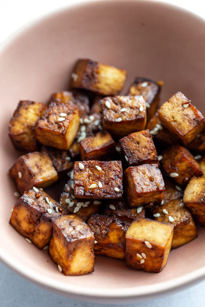 pale pink bowl filled with crispy tofu and sprinkled with sesame seeds