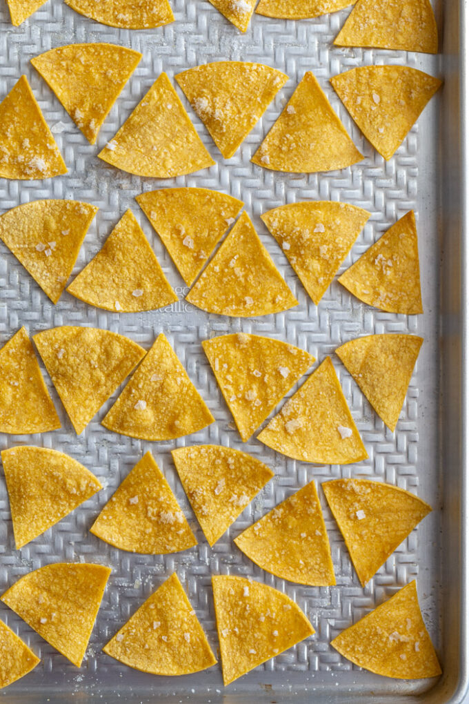 homemade tortilla chips lined up on a baking sheet