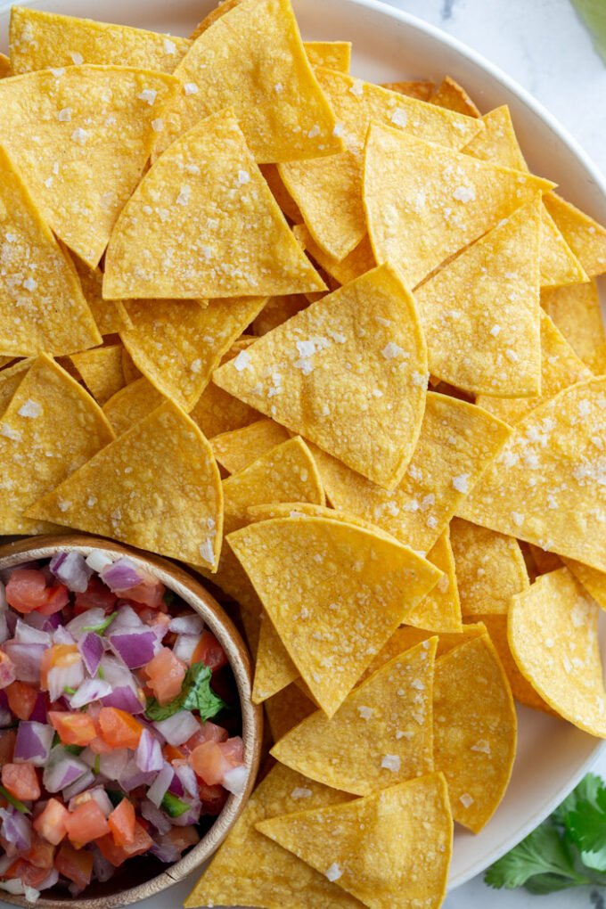 large plate of homemade tortilla chips with a bowl of pico de gallo on the plate