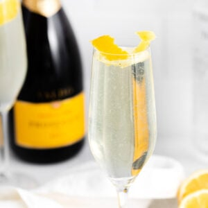 French 75 drink near a bottle of champagne