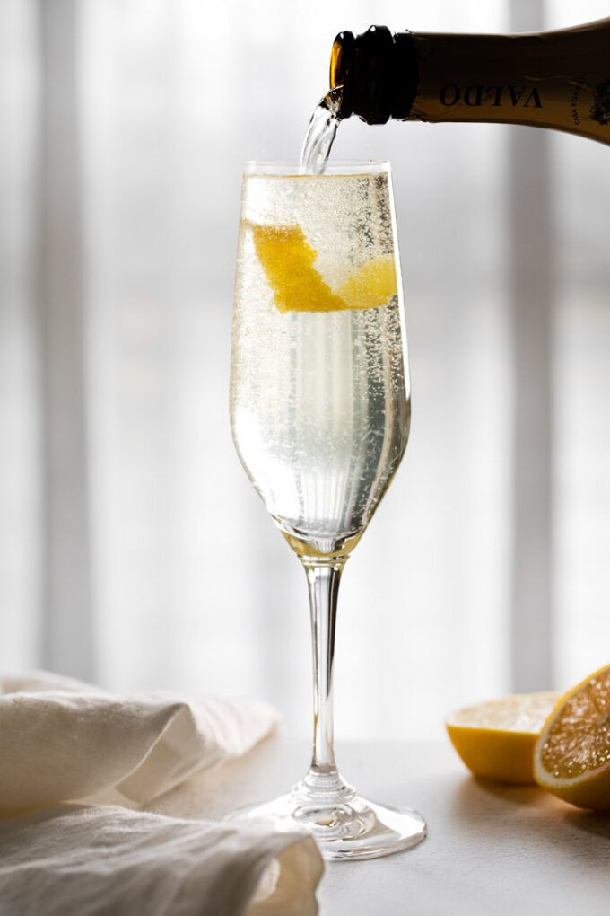 pouring champagne into a glass with a lemon twist