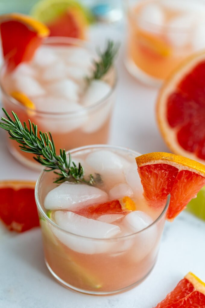 small clear glass filled with a pink cocktail that's a grapefruit gin and tonic garnished with a grapefruit slice and fresh rosemary. More drinks in the background