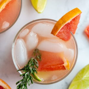 top down shot of small clear glass filled with a pink cocktail that's a grapefruit gin and tonic garnished with a grapefruit slice and fresh rosemary. More drinks in the background