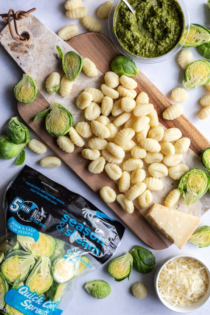 gnocchi on a wood board with brussels sprouts and pesto in the scene. a package of ocean mist quick cook sprouts in the corner