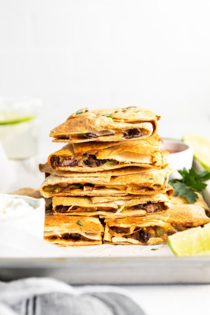 crispy vegetarian quesadillas stacked in a tall pile so you can see what's inside of them