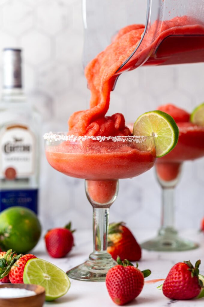 frozen strawberry margarita in a margarita glass being poured from a blender. another drink and a bottle of tequila in the background with fresh fruit around