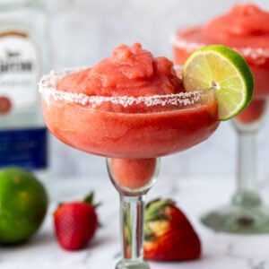 margarita glass filled with a red strawberry frozen margarita and a lime on the rim. more fruit and tequila bottle in the background