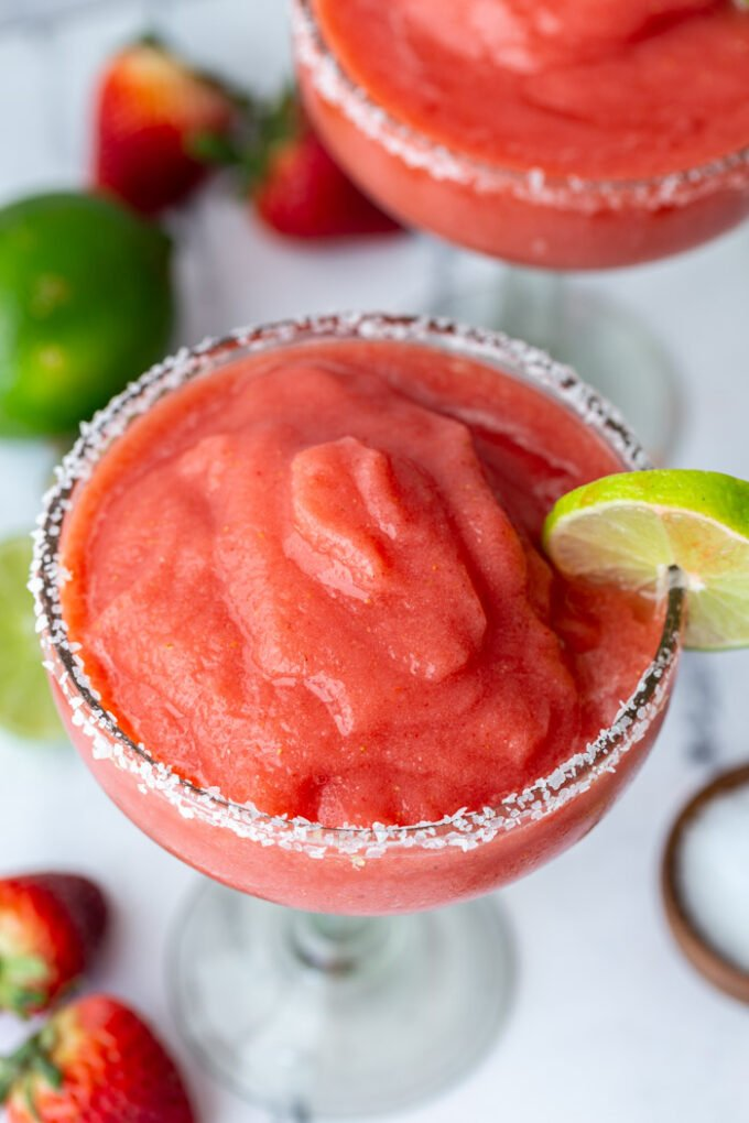 up close shot of a frozen strawberry margarita with a lime wedge on the side