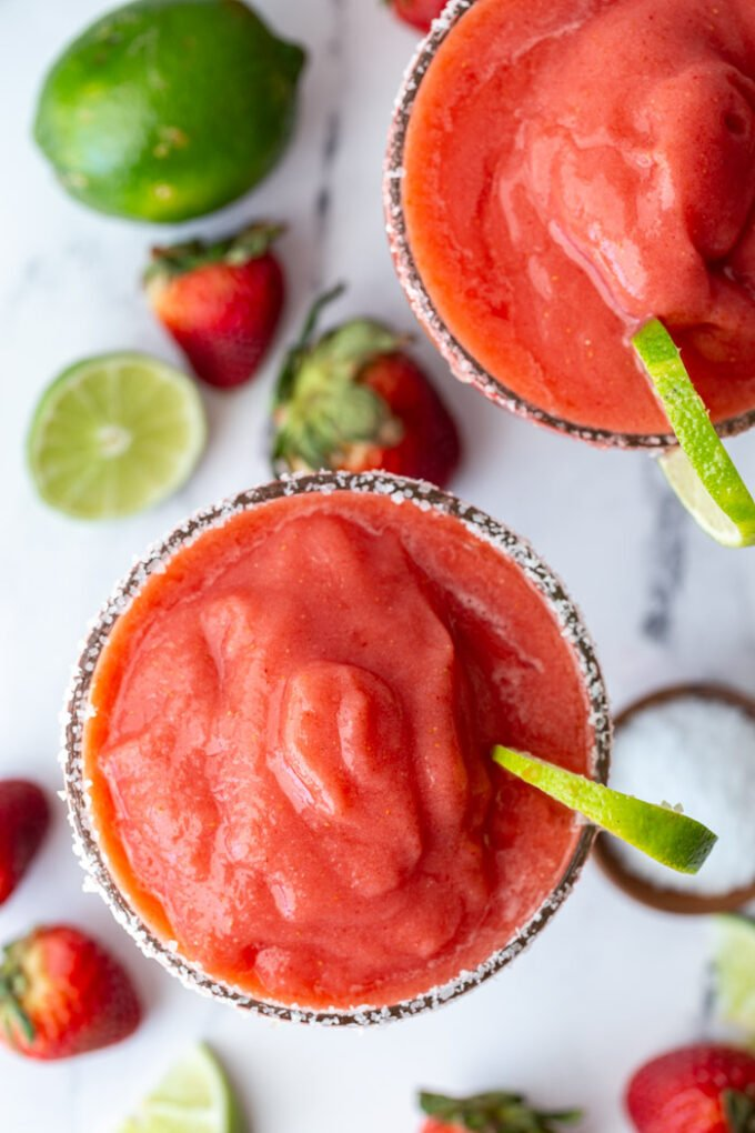 top down shot of 2 frozen strawberry margaritas with fresh limes and strawberries in the scene