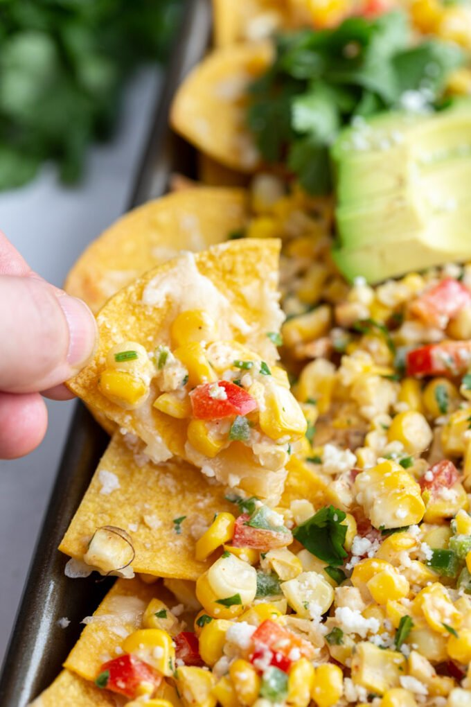 hand holding up a tortilla chip with street corn salad on it and more nachos in the background