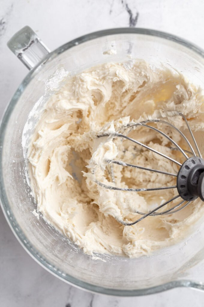 buttercream cookie frosting in the base of a stand mixer with the whisk attachment sitting in the bowl