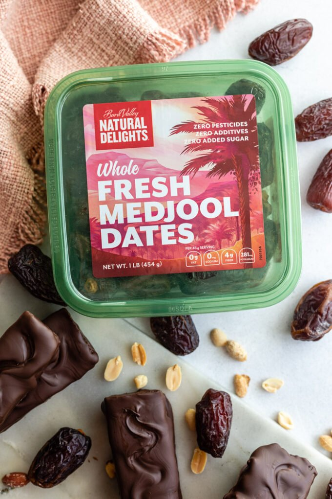homemade snickers bars next to a tub of whole fresh medjool dates from natural delights