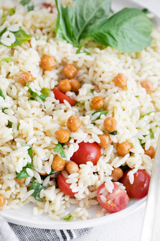 orzo pasta salad topped with chickpeas and cherry tomatoes