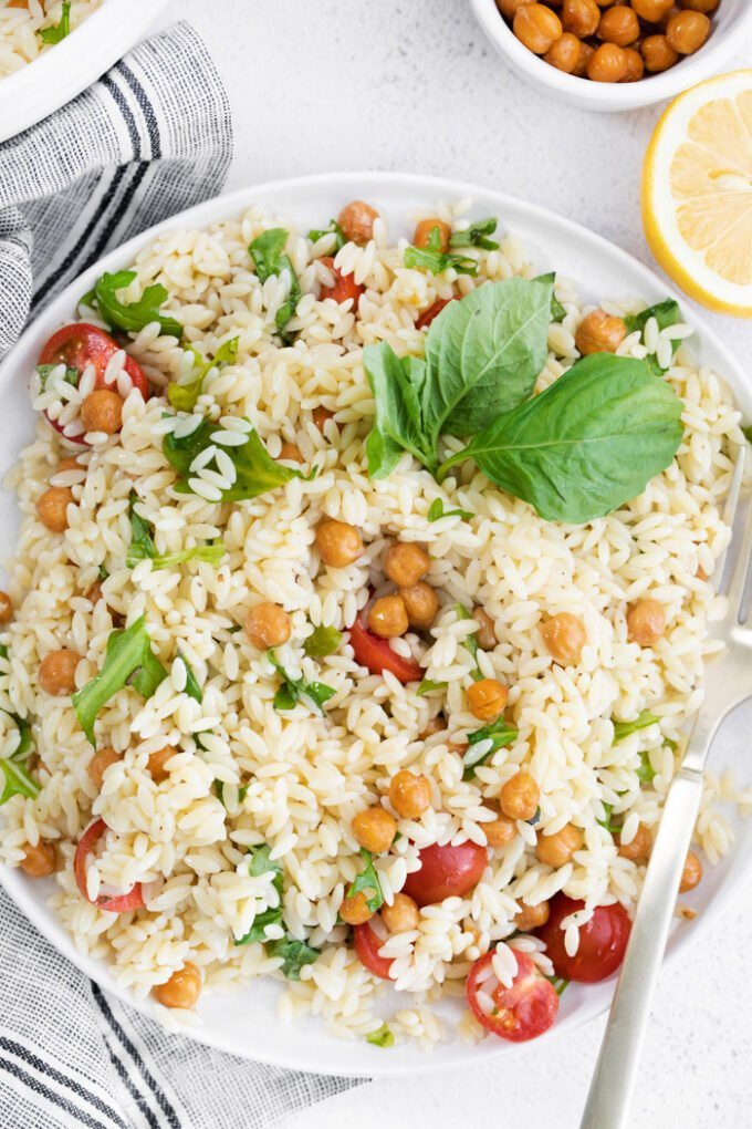 orzo pasta salad topped with chickpeas and tomatoes
