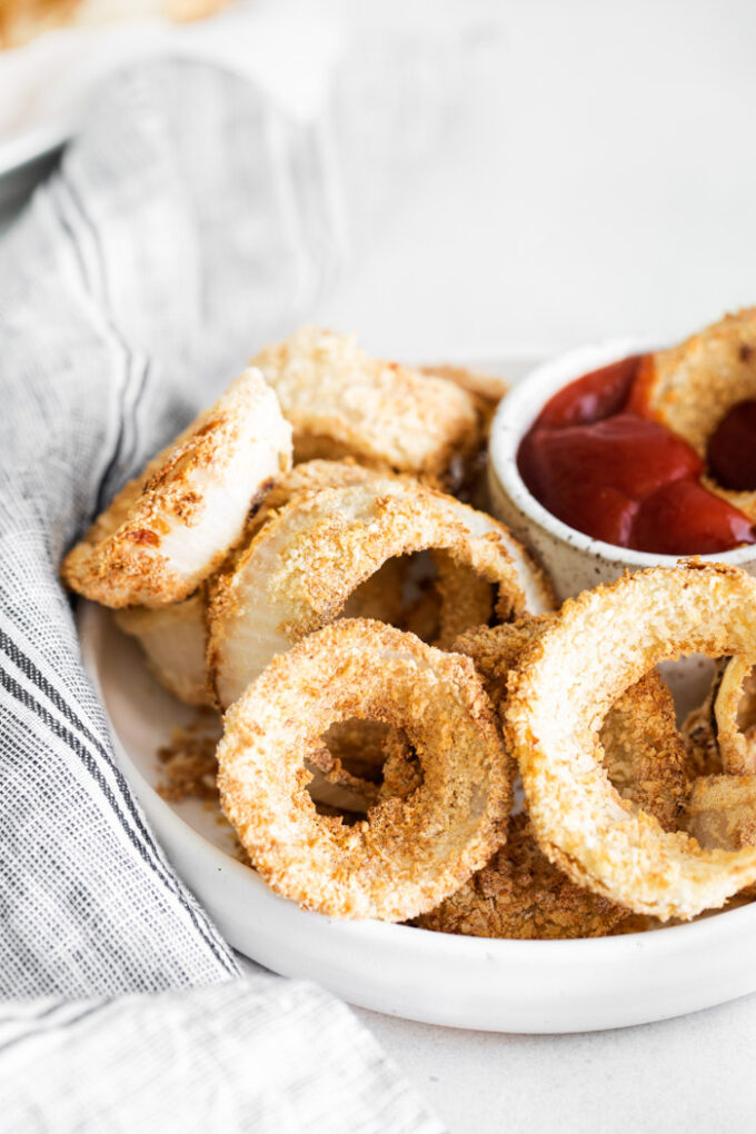 air fryer onion rings in a basket served with ketchup