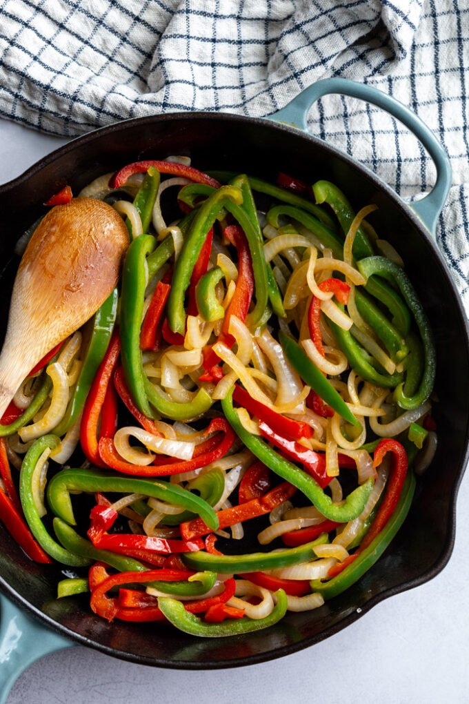green + red bell peppers and onion being sauteed in a large cast iron skillet