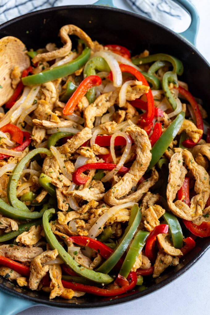 soy curls fajitas with soy curls and sauteed onion and green + red bell pepper in a large cast iron skillet