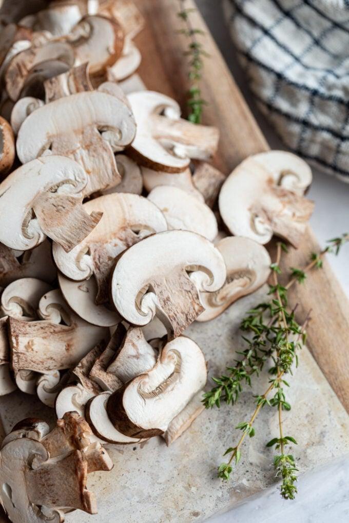 sliced mushrooms on a wooden cutting board