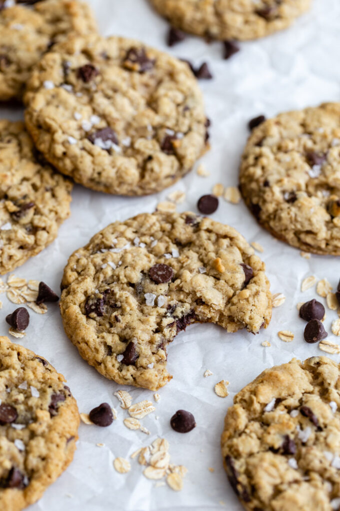 chocolate chip oatmeal cookies on parchment paper with oats and chips surrounding it