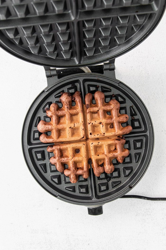 cooking chocolate waffles on a waffle iron