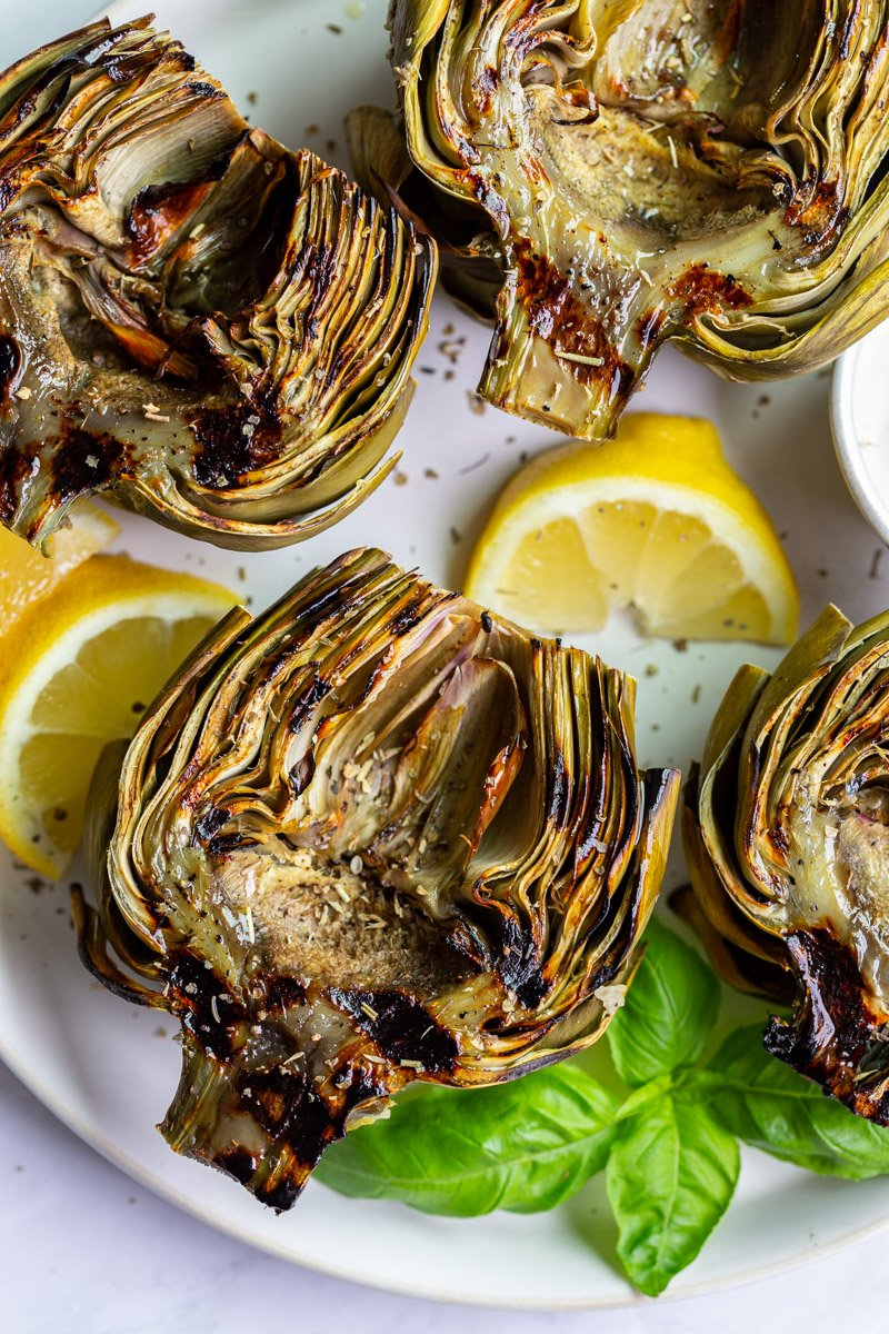 large plate with 4 grilled artichokes on it and lemon slices on the plate