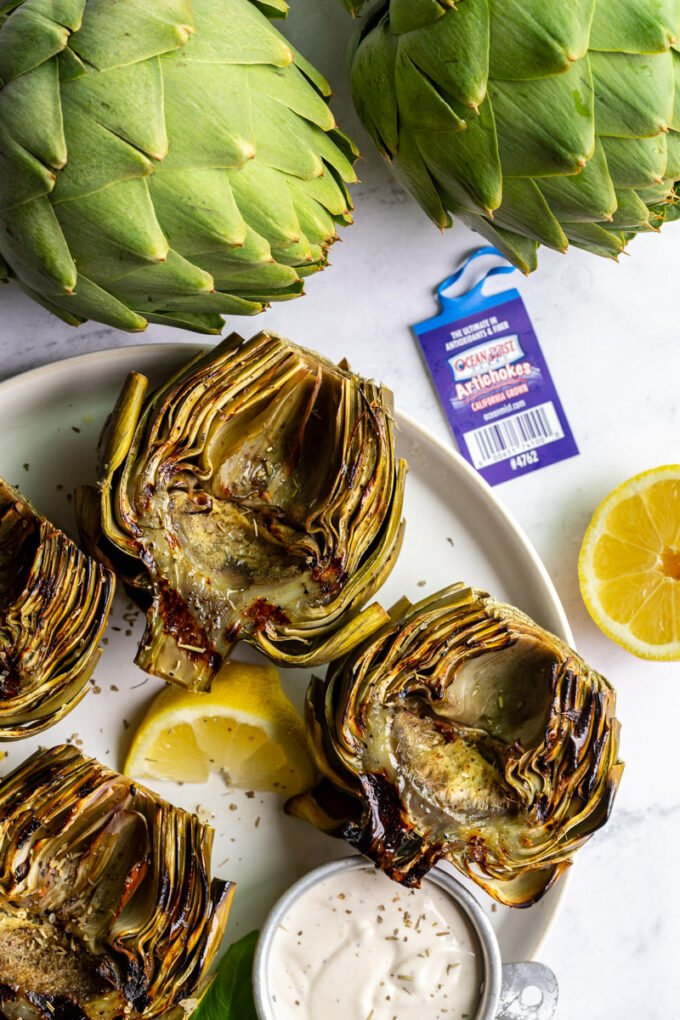 large plate with 4 grilled artichokes on it and lemon slices on the plate. fresh artichokes in the corner