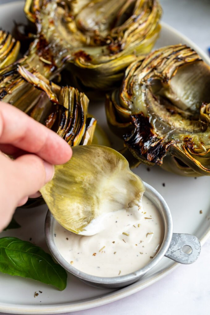 large plate with 4 grilled artichokes on it and lemon slices on the plate. hand holding an artichoke leaf in dip