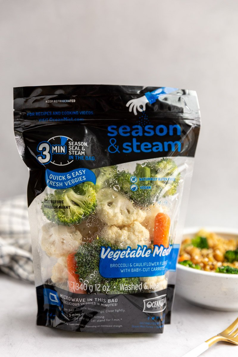 bag of ocean mist season and steam vegetable medley standing up on a table with a bowl of veggie ramen behind it