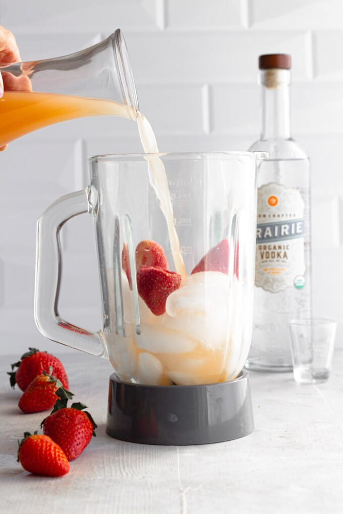 blender full of ice and strawberries with grapefruit juice being poured in