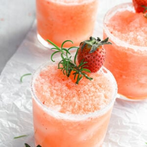 small glass with a frozen salty dog slushie with fresh strawberries and rosemary on top