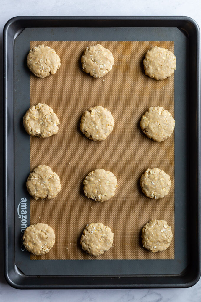 large cookie sheet with uncooked oatmeal cookies on it
