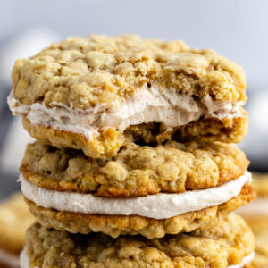 oatmeal cream pies stacked on top of each other on a wood and marble board. a bite taken out of the top cookie